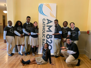 Cristo Rey students in front of AM 820 sign