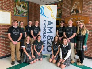 Newark Catholic students in front of AM 820 sign