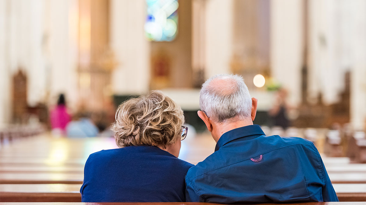 Couple sitting heads together in a Church